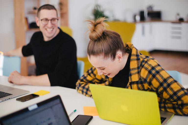 Fotografia di due giovani colleghi che ridono mentre lavorano